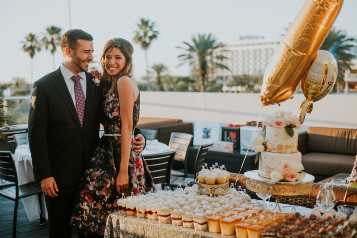 engaged couple with dessert table at engagement party